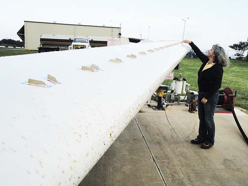 Anni Brogan, owner and president of Micro Aerodynamics, inspecting vortex generators (VGs) on the wings of a small aircraft